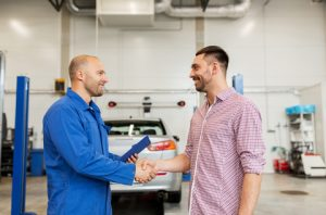 Two men shaking hands at an auto body repair shop