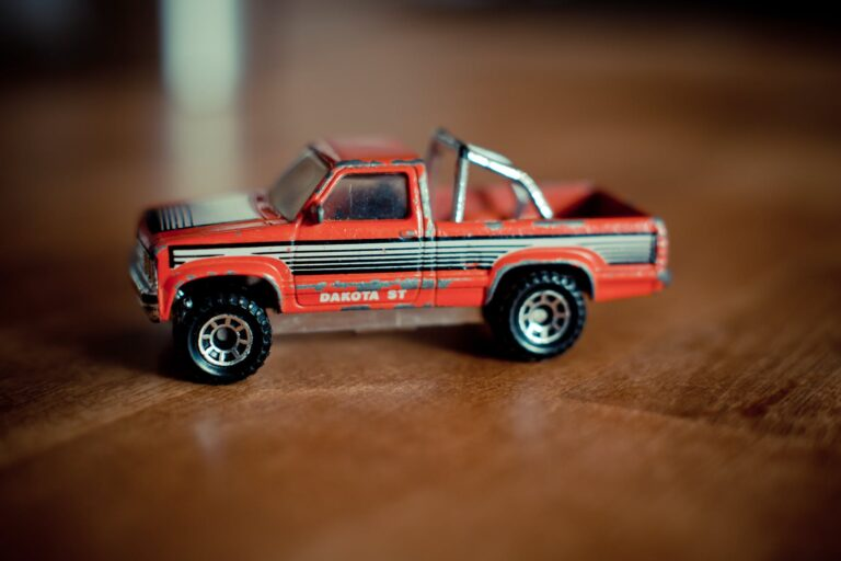 red-toy-truck-sitting-on-a-wooden-table